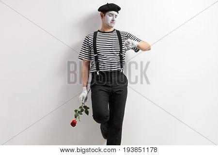 Mime with a red rose leaning against a wall and looking at an imaginary watch