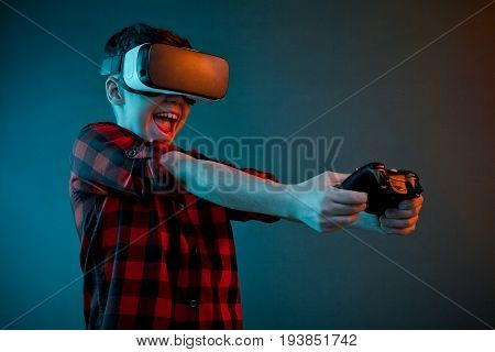 Laughing kid in checkered shirt playing gamepad while wearing VR goggles on studio background.