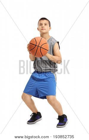 Full length portrait of a boy about to throw a basketball isolated on white background