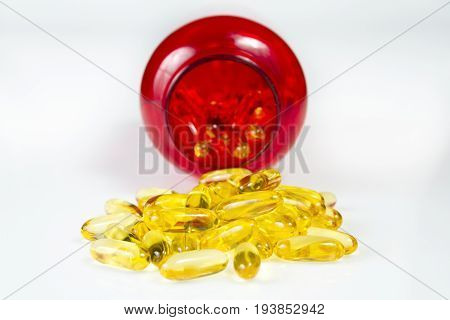 Container of fish oil gel capsules of omega 3. Close up capsules fish oil on white surface. The supplement high vitamin E omega 3 and DHA.