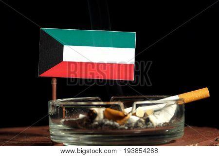 Kuwaiti Flag With Burning Cigarette In Ashtray Isolated On Black Background