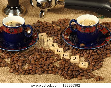 Melbourne, Australia - June 24, 2017: Coffee beans, two ornate cups, tamper and a group handle with wooden letter tiles arranged to form the word