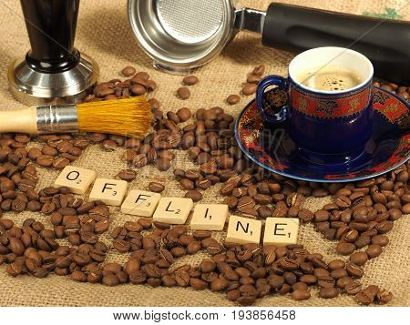 Melbourne, Australia - June 24, 2017: Coffee beans, one cup, tamper and a group handle with wooden letter tiles arranged to form the word