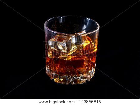 Glass of whiskey or bourbon with ice on black stone table