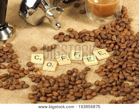 Melbourne, Australia - June 24, 2017: Coffee beans, glass mug and tamper in front of a group handle with wooden letter tiles arranged to form the word