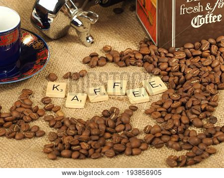 Melbourne, Australia - June 24, 2017: Coffee beans, cup,  group handle and tin box with wooden letter tiles arranged to form the word