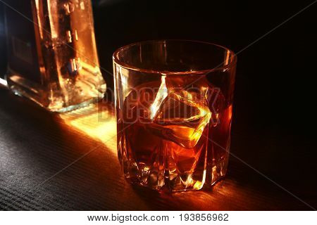 Bottle and Glass of whiskey or bourbon with ice on black stone table