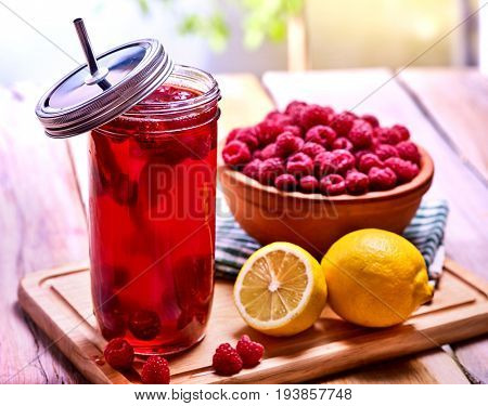 Cold non alcoholic cocktail with lemon half and raspberries bowl. Nonalcoholic beverage in cocktail glass with cocktail straw on wooden board. Table setting rural style with drinks in village.