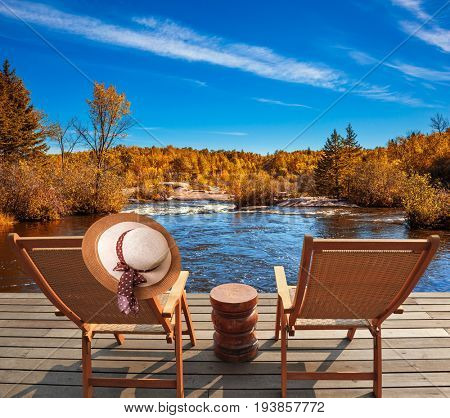 Two beach chairs and hat on the riverbank. Lovely place to relax. Winnipeg River, Old Pinawa Dam Park. The concept of recreational tourism