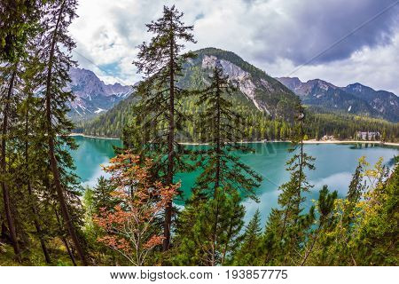 The concept of environmental and hiking. Walk around the lake Lago di Braies, South Tyrol, Italy.  Water reflects mountains and forest