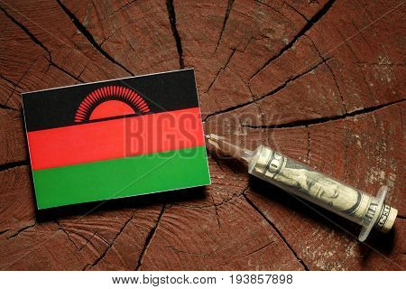 Malawi Flag On A Stump With Syringe Injecting Money In Flag