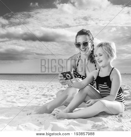 Happy Young Mother And Daughter On Seacoast Viewing Photos