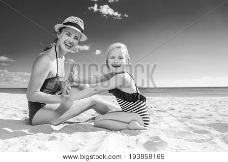 Smiling Young Mother And Child In Swimsuit On Seacoast Playing