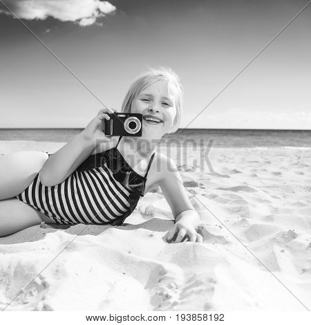 Smiling Child On Seacoast Taking Photo With Digital Camera