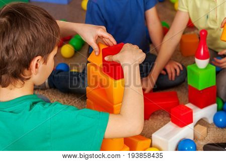 Children building blocks in kindergarten. Group kids playing toy on floor. Top view of interior preschool. Building tower of cubes. Independent children's creativity