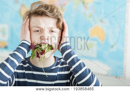 Distressed Boy With Mouth Full Of Lettuce