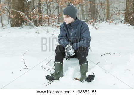 Calm Child Sitting Down After Playing In The Snow