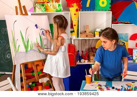 Children painting finger on easel. Group of kids girl learn paint in class school. Child picture on background. Students draw spring flowers. Independent children's creativity