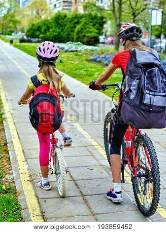 Bicycle path and sign with children. Girls wearing bicycle helmet with rucksack ciclyng ride. Kids are on yellow bike lane leave city. Children travel unaccompanied.