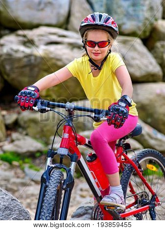 Child on bicycle ride mountain. Girl traveling in summer park. Cycling person wearing helmet . Sport trip is good for children health. Independent and freedom of child idea.