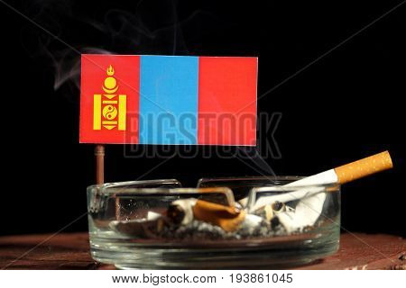 Mongolian Flag With Burning Cigarette In Ashtray Isolated On Black Background