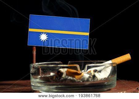 Nauru Flag With Burning Cigarette In Ashtray Isolated On Black Background