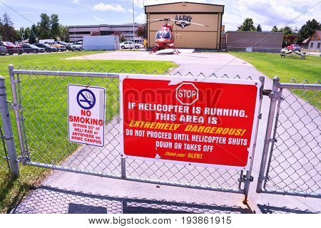 KALISPELL, MONTANA, USA - June 19, 2017: Helicopter warning sign on a gate in front of the ALERT air ambulance helipad