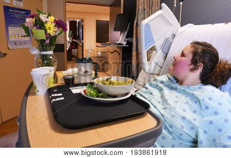 KALISPELL, MONTANA, USA - June 19, 2017: Patient lies in bed with a bowl of hospital food on her tray