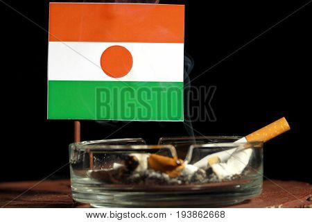 Niger Flag With Burning Cigarette In Ashtray Isolated On Black Background
