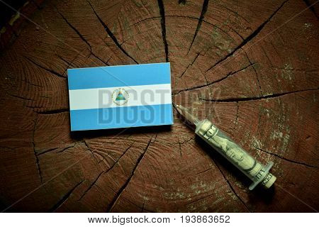 Nicaraguan Flag On A Stump With Syringe Injecting Money In Flag