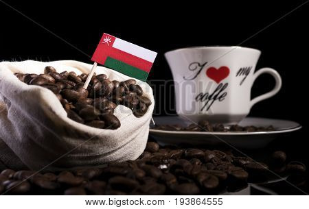 Omani Flag In A Bag With Coffee Beans Isolated On Black Background