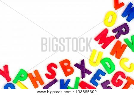 Corner border of colorful toy magnetic alphabet letters over a white background