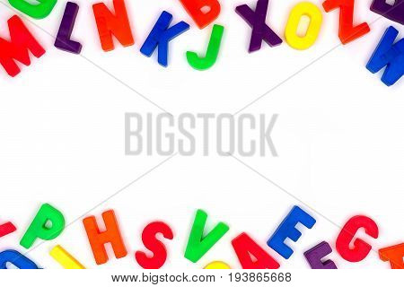 Double Border Of Colorful Toy Magnetic Alphabet Letters Over A White Background