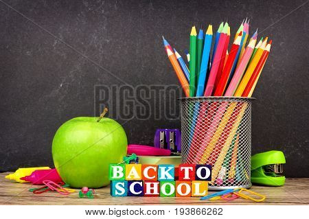 Colorful Back To School Toy Wooden Blocks With School Supplies And Chalkboard In Background