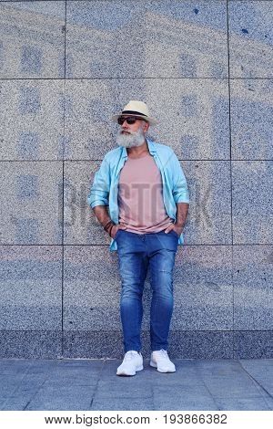 Full-length image of male having beard and stylish cloth, wearing sunglasses and white sneakers, mid shot