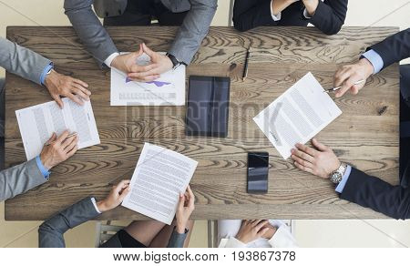 Top view of confident business men in suits sitting at wooden table and discussing new contract terms before signing it