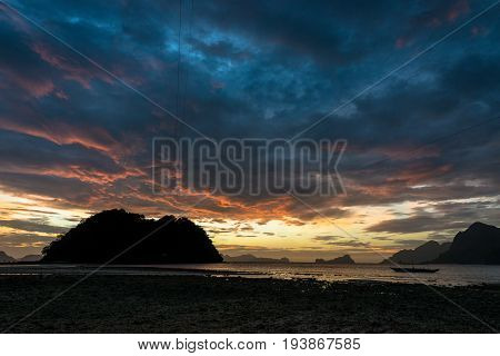 EL NIDO, PALAWAN, PHILIPPINES - MARCH 29, 2017: Horizontal picture of a colorful clouds at the sunset of Las Cabanas Beach.