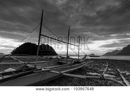 EL NIDO, PALAWAN, PHILIPPINES - MARCH 29, 2017: Black and white picture of traditional filippino boats at El Nido bay.