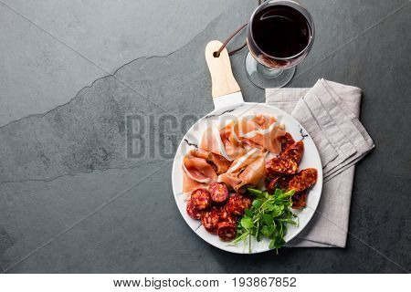 Spanish Ham Serrano And Salami On White Marbled Plate An Red Wine. Top View.