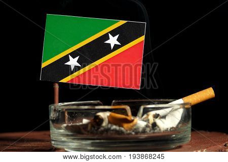Saint Kitts And Nevis Flag With Burning Cigarette In Ashtray Isolated On Black Background