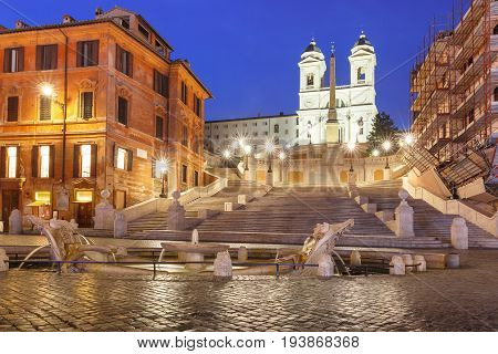 Monumental stairway Spanish Steps, seen from Piazza di Spagna, and the Early Baroque fountain called Fontana della Barcaccia or Fountain of the ugly Boat during morning blue hour, Rome, Italy.