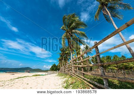 EL NIDO, PALAWAN, PHILIPPINES - APRIL 01, 2017: Wide angle view picture of coconut trees and white sand at Nacpan Beach.
