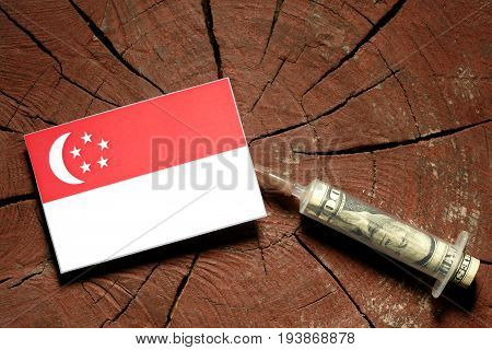 Singaporean Flag On A Stump With Syringe Injecting Money In Flag