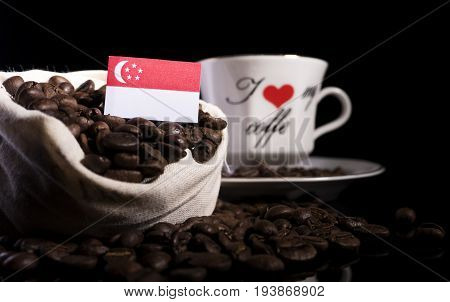 Singaporean Flag In A Bag With Coffee Beans Isolated On Black Background