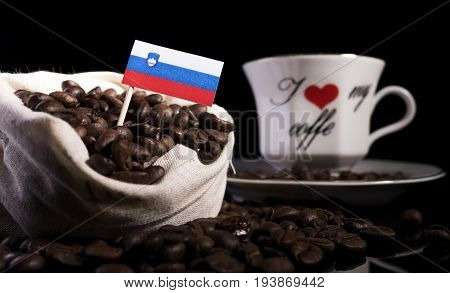 Slovenian Flag In A Bag With Coffee Beans Isolated On Black Background
