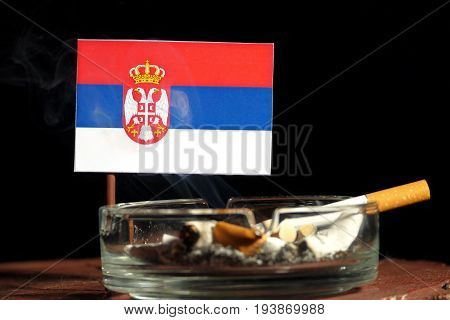 Serbian Flag With Burning Cigarette In Ashtray Isolated On Black Background