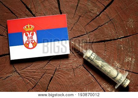 Serbian Flag On A Stump With Syringe Injecting Money In Flag