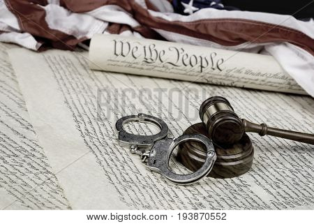 The United States Constitution rolled up on an American flag with a gavel and handcuffs in the foreground.
