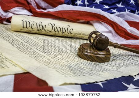 The United States Constitution rolled up on an American flag with a gavel in the foreground. Room for copy along the left of the image.
