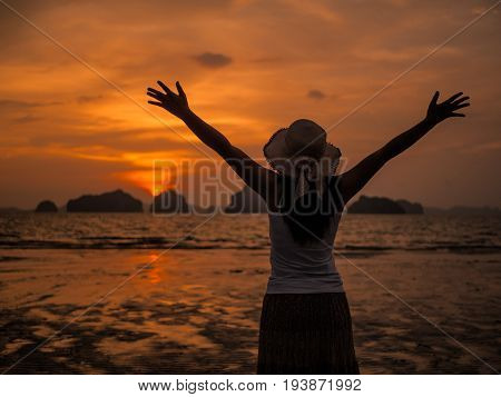 Silhouette of woman wearing hat with open arms under the sunrise near the sea. Summer concept.